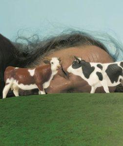 Des figurines de vache devant un homme qui dort (La Vache et son Prisonnier)